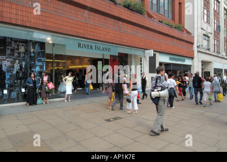 Shoppers on pavement outside store windows River Island clothing shop front & entrance in Oxford Street West End - Stock Photo