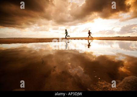 Two children running along the beach on a cloudy day, Reflection, Segeltorpstrandet, Halmstadt, Skane, Sweden - Stock Photo