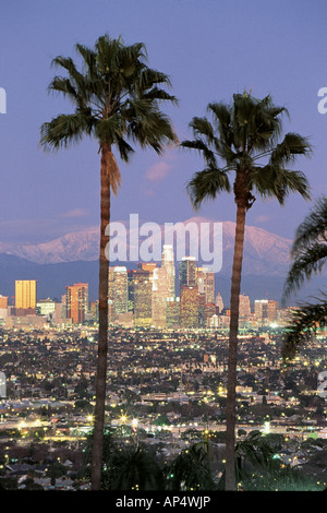 Los Angeles skyline with two palm trees in the winter and snowy Mount Baldy in the background. - Stock Photo