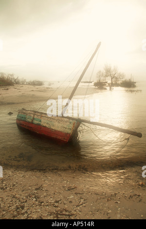 Dhow sailing and fishing boat lying on it s side on the beach on an early misty morning - Stock Photo
