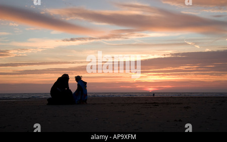 mother and daughter on a beach at sunset - Stock Photo