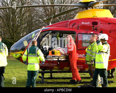 Paramedic with injured person and emergency services personnel at air ambulance - Stock Photo