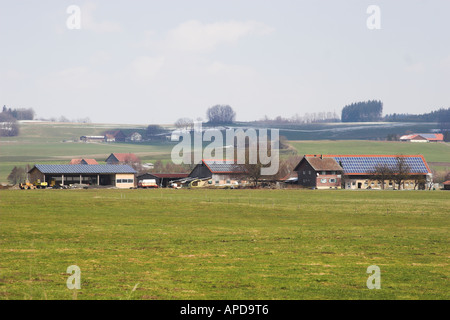 Farm buildings roofs in Southern Germany covered with PV (photovoltaic) cells for electricity generation for sale - Stock Photo