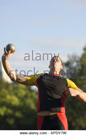 Male athlete throwing shot put - Stock Photo