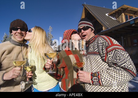 Two couples kissing on the deck of a ski lodge on a sunny day in winter at Northstar ski resort near Lake Tahoe - Stock Photo