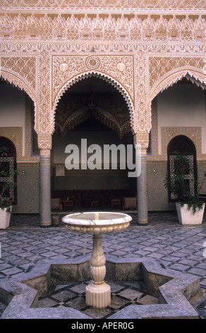 Palace courtyard is surrounded by islamic arches with opulent arabesque calligraphy with mugarnas a stucco honeycomb - Stock Photo