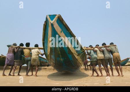 Fisherman carry boat on the beach Puri Orissa India - Stock Photo