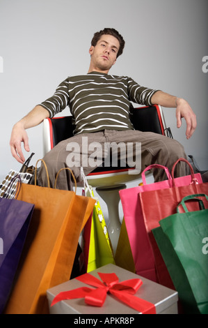 Tired young man with shopping bags - Stock Photo