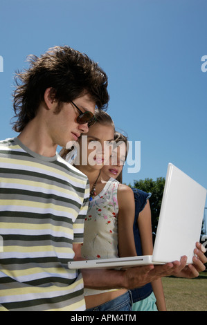 Three teenagers with notebook - Stock Photo