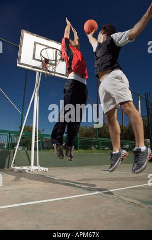 Two young men playing basketball - Stock Photo