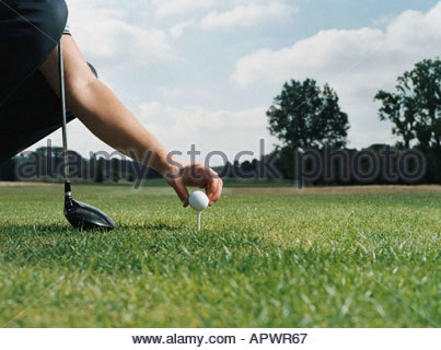 Placing a golf ball on the tee - Stock Photo