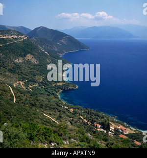 View from west coast along hilly coastline of Ithaca Island with winding roads & Cephalonia hazy in background The - Stock Photo