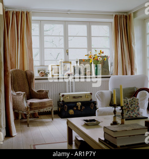 sitting room with armchairs, coffee table and old luggage as a side table - Stock Photo