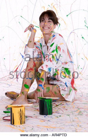 Attractive young brunet woman in a mens dress shirt covered in colorful paint - Stock Photo