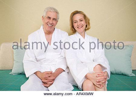 Senior couple sitting on a bed - Stock Photo