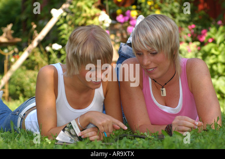 junge Mädchen mit Zeitschrift | young girls lying in the grass with a magazine - Stock Photo