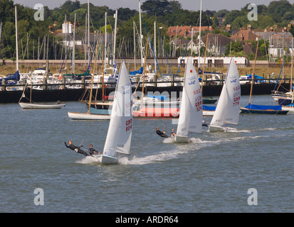 Trio of Olympic Class 470 two man racing dinghies under full sail in line with hundreds of yacht masts beyond Lymington - Stock Photo