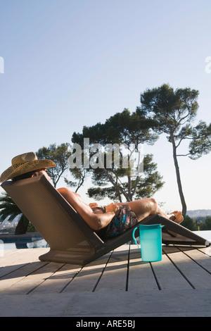 Man lying on sun lounger - Stock Photo