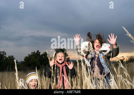 Group of kids jumping in long grass - Stock Photo