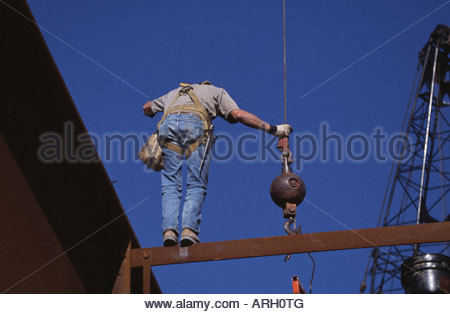 Low angle view of a steelworker working at a bridge construction site - Stock Photo