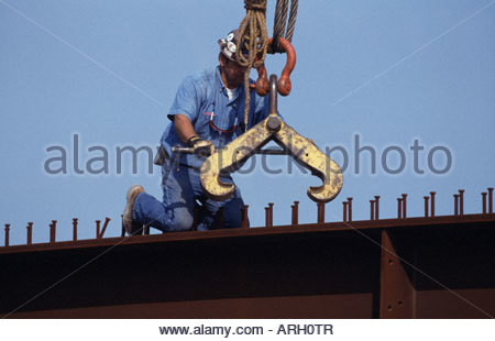Steelworker attaching crane clamp to a plate girder - Stock Photo