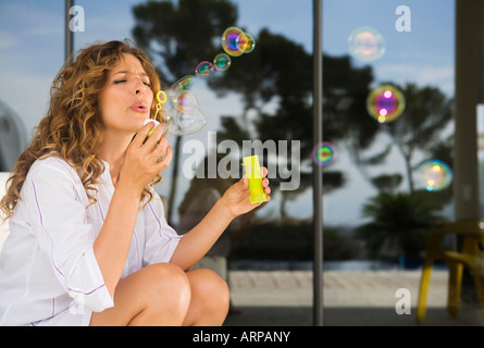 Woman blowing bubbles - Stock Photo