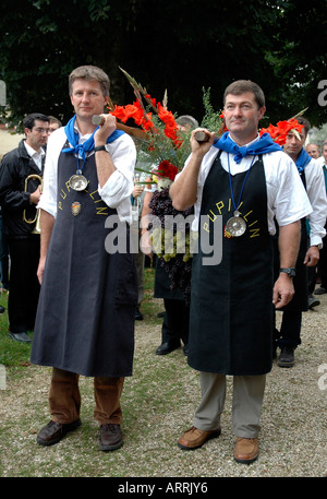 In Pupillin's annual wine festival, or biou, in the French Jura, strong men parade with the traditional huge bunch - Stock Photo