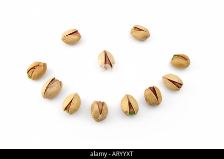 Smiling face made from pistachio nuts - Stock Photo