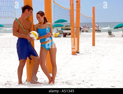 Caucasian brunette couple in 20 s on beach beside volleyball net Wearing blue swim suits man with volleyball woman - Stock Photo