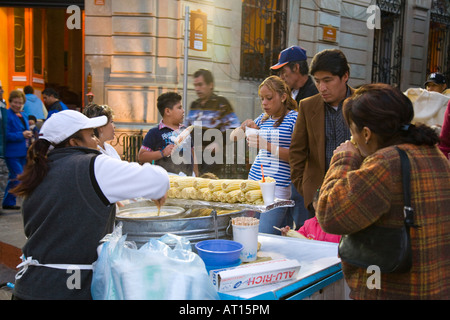 MEXICO Guanajuato Mexican woman selling corn on the cob and creamed corn in cups on street customers eating and - Stock Photo