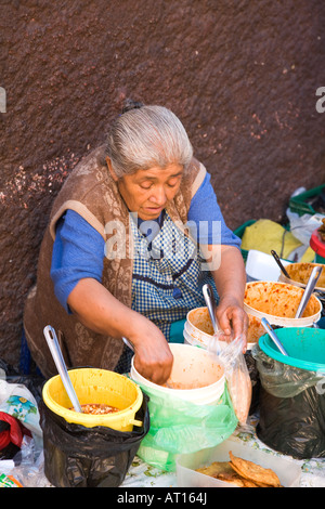 MEXICO Guanajuato Older Mexican woman with white hair dishing out food from buckets on street - Stock Photo