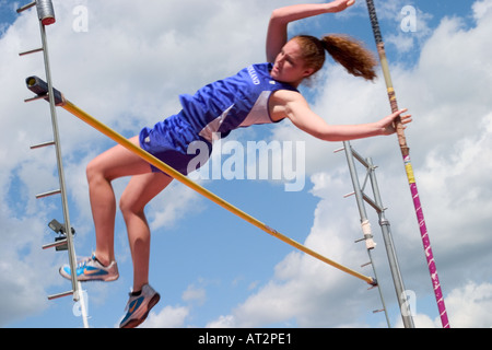 High school girl attempting a pole vault in a track and field meet - Stock Photo