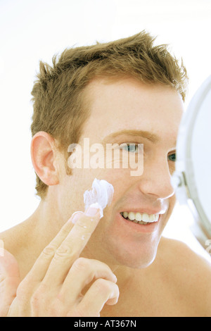 A man applying moisturizer - Stock Photo