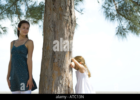 Two sisters playing hide-and-seek together - Stock Photo