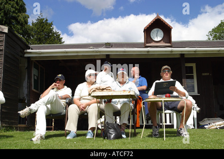 Cricket match scorekeeper and players watch a game of English village cricket in summer at Horrington Somerset - Stock Photo