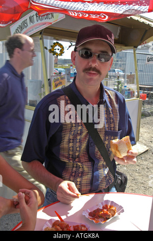 A tourist from New Zealand having a currywurst at a chips stand on Potsdamer Platz. Berlin 2004. - Stock Photo
