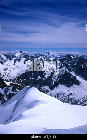 view north west from the Aiguille du Midi with climbers ascending snow covered ridge in foreground, French alps - Stock Photo