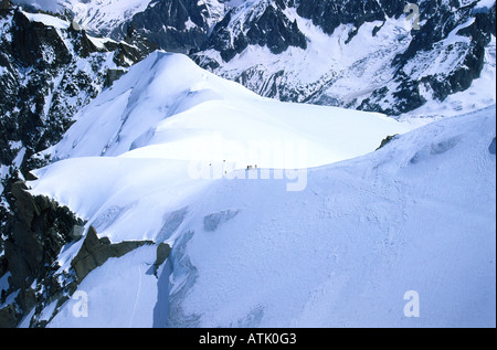 Climbers on the steep ridge up to the Aiguille du Midi from col du Midi, French alps - Stock Photo