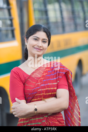 Portrait of a mid adult woman smiling near a school bus - Stock Photo