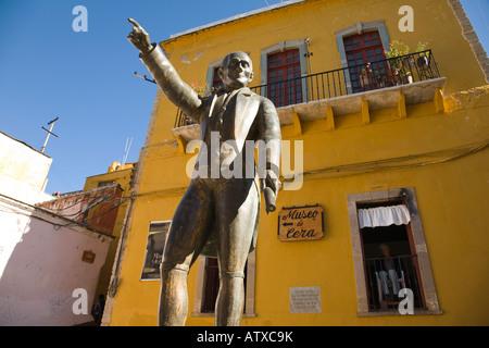 MEXICO Guanajuato Statue in plaza outside Wax Museum Casa de Cera man sitting in open doorway - Stock Photo