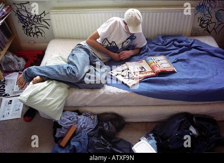 Teenaged boy lying on bed reading magazines. - Stock Photo