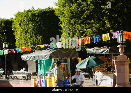 MEXICO San Miguel de Allende Cut out paper flags decorate plaza around El Jardin street vendors selling food and - Stock Photo