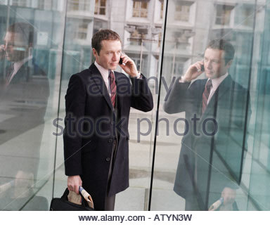 Businessman in doorway on cellular phone - Stock Photo