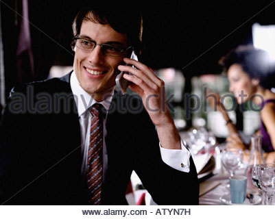 Businessman in restaurant on cellular phone - Stock Photo
