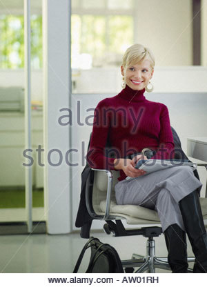 Businesswoman sitting in office with paperwork - Stock Photo