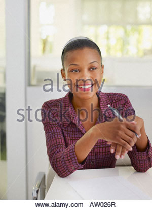 Businesswoman in office with notepad - Stock Photo