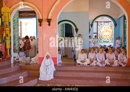 A female CAO DAI PRIEST sits before her followers inside the CAO DAI GREAT TEMPLE TAY NINH VILLAGE VIETNAM - Stock Photo