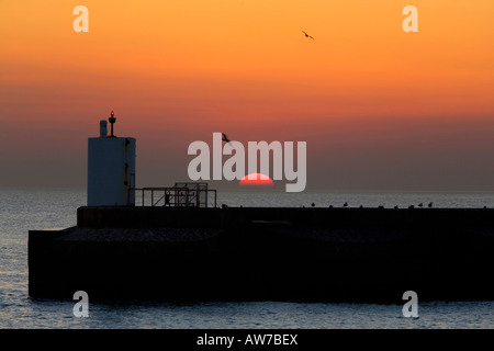 Setting sun falls behind lighthouse on Pier brighton marina uk - Stock Photo