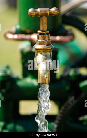 an outside tap in a garden running with fresh water turned on for watering the plants in the garden from a brass - Stock Photo