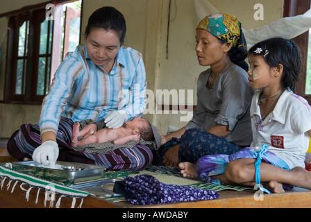 Medic cleaning a newly born´s umbilical cord, Kou Kou Clinic, Swe Kou Kou village, IDP-Area bordering Thailand near - Stock Photo